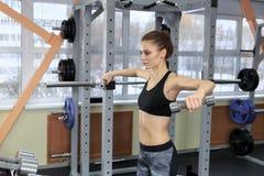 Mooie geschiktheidsvrouw met het opheffen van domoren Sportieve vrouw die lichte gewichten opheffen Geschikt meisje die de bouwsp Stock Foto