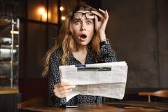Mooie geschokte opgewekte jonge vrouwenzitting in koffie die binnen krant lezen royalty-vrije stock foto's