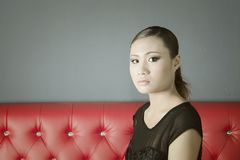Mooie gezichtsvrouw in zwarte kledingszitting op rode bank Stock Foto