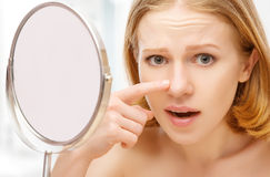 Mooie gezonde vrouw bang gemaakte zaag in de de spiegelacne en rimpels Royalty-vrije Stock Foto's