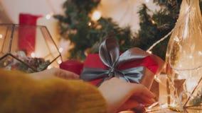 Mooie gift in de handen van mensen De gift van het nieuwjaar met een rood lint, spar op de lijst De man maakte het zelf en is stock video