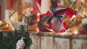 Mooie gift in de handen van mensen De gift van het nieuwjaar met een rood lint, spar op de lijst De man maakte het zelf en is stock videobeelden