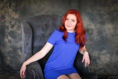 Mooie ginger-haired vrouw in blauwe kledingszitting in grijze leunstoel royalty-vrije stock foto