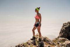 Mooie gir bevindt zich op de rand van een beboste klip en bekijkt het glanzende overzees Stock Foto