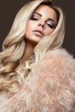 Mooie glamour blondie vrouw in bontjas, die make-up en krullen gelijk maken De schoonheid van het gezicht Royalty-vrije Stock Foto's