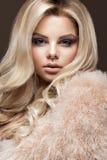 Mooie glamour blondie vrouw in bontjas, die make-up en krullen gelijk maken De schoonheid van het gezicht Royalty-vrije Stock Fotografie