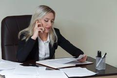Mooie glimlachende bedrijfsvrouw die bij haar bureau met documenten werken en op de telefoon spreken Stock Foto