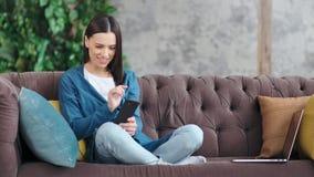 Mooie glimlachende binnenlandse jonge vrouw die in sociale netwerken babbelen die smartphone gebruiken stock video