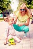 Mooie glimlachende emotionele moeder met haar dochter die sk berijden royalty-vrije stock afbeeldingen