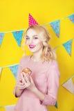 Mooie glimlachende jonge blondevrouw met een cake Viering en partij Stock Foto