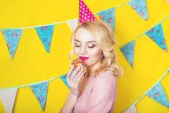 Mooie glimlachende jonge blondevrouw met een cake Viering en partij Stock Fotografie