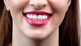Mooie glimlachende jonge vrouw met perfecte huid, rode lippenstift en tanden Sluit omhoog Langzame Motie stock video