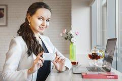 Mooie glimlachende onderneemster en het tonen van adreskaartje in haar handen Stock Fotografie