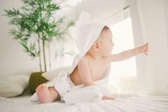 Mooie glimlachende pasgeboren babyjongen omvat met witte bamboehanddoek met pretoren Zittend op een wit brei, heldere inter van d stock afbeeldingen