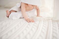 Mooie glimlachende pasgeboren babyjongen omvat met witte bamboehanddoek met pretoren Zittend op een wit brei, heldere inter van d stock fotografie