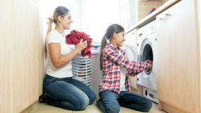 Mooie glimlachende tiener die moeder in wasserijruimte helpen stock foto