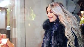 Mooie glimlachende vrouw die het venstervertoning bekijken die van de glaswinkel door Kerstmislichten gelijk te maken wordt omrin stock video