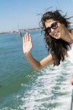 Mooie glimlachende vrouw die op een boot met wind in het haar varen Stock Foto