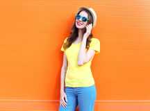 Mooie glimlachende vrouw die op smartphone over kleurrijke sinaasappel spreken stock fotografie