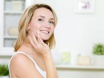 Mooie glimlachende vrouw die room op gezicht toepast royalty-vrije stock afbeelding