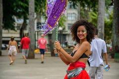 Mooie glimlachende vrouw met het krullende haar en neus doordringen, die purpere vlag houden in Bloco Orquestra Voadora, Carnaval Royalty-vrije Stock Foto's