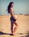 Mooie glimlachende vrouw met manierzak het stellen op strandbac royalty-vrije stock foto