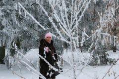 Mooie glimlachende vrouw onder snow-covered bomen stock foto