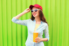 Mooie glimlachende vrouw in zonnebril met kop van vruchtensap over kleurrijke groen Stock Fotografie