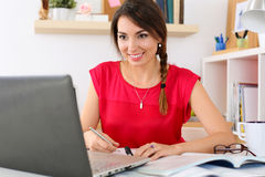 Mooie glimlachende vrouwelijke student die de online onderwijsdienst gebruiken Stock Afbeeldingen