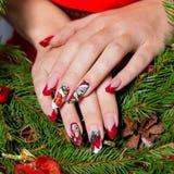 Mooie goed-verzorgde handen van een jong meisje met lange valse acrylspijkers met een feestelijk Kerstmispatroon op de spijkers Stock Foto