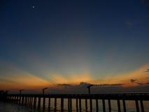 Mooie gouden na gloed en de toenemende maan op donkerblauwe hemel over de brug aan het overzees Royalty-vrije Stock Fotografie