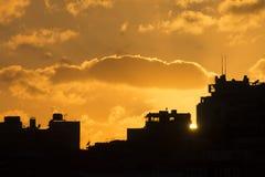 Mooie gouden zonsondergang achter zwarte silhouetten van gebouwen in Istanboel Stock Foto