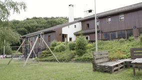 Mooie groene buitenkant van een modern huis op grijze hemelachtergrond actie Yard met groen gras en terrasgebied, schommeling stock videobeelden