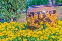 Mooie grote aarden kruik met gele die draak in de gele bloemtuin wordt gevormd royalty-vrije stock foto