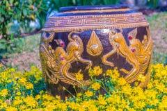 Mooie grote aarden kruik met gele die draak in de gele bloemtuin wordt gevormd stock foto's