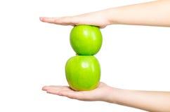 In mooie handen een groene die appel twee, op witte achtergrond wordt geïsoleerd Stock Foto