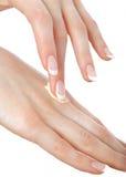 Mooie handen met Franse manicure en room Stock Fotografie