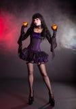 Mooie heks in purper en zwart gotisch Halloween-kostuum Stock Foto's