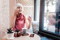Mooie heldere oude vrouw die haar nauwkeurig kapsel verbeteren royalty-vrije stock afbeelding