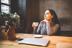 Mooie het bedrijfsmeisje drinken koffie van witte die kop in restaurant met Kerstmisdecor wordt verfraaid het zitten dichtbij ven royalty-vrije stock afbeelding