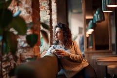 Mooie het bedrijfsmeisje drinken koffie van witte kop in comfortabele koffie het zitten dichtbij venster bij een houten lijst Gek stock foto's