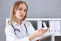 Mooie het glimlachen vrouwelijke artsentribune in bureauportret Stock Foto