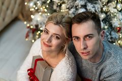 Mooie het houden van jongerenomhelzingen op Kerstboomachtergrond royalty-vrije stock foto's
