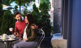 Mooie het houden van paar het besteden tijd samen in openluchtkoffie stock afbeeldingen