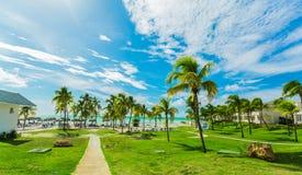 Mooie het uitnodigen mening die van tropische tuin op Cubaans Varadero strand, rustige turkooise tedere oceaan, mensen in backgro stock foto's