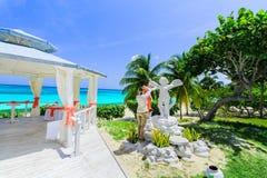 mooie het uitnodigen mening van een jong meisje, dame het verfraaien, die strandgazebo voor een rustige oceaan, blauwe hemel van  stock afbeeldingen