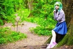 Mooie hipster alternatieve jonge vrouw met groen haar in park stock foto