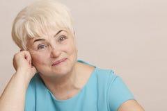 Mooie hogere blonde vrouw in blauwe kleding Stock Foto
