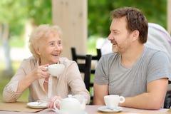 Mooie hogere dame met zijn rijpe zoon het drinken thee in in openlucht koffie of restaurant Bejaarde damelevensstijl stock afbeeldingen