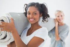 Mooie housemates die opgerolde deken dragen Royalty-vrije Stock Afbeelding